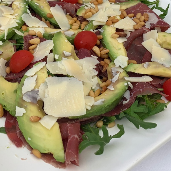 Bresaola-Schinken mit Avocado, gerösteten Pinienkernen und gehobeltem Parmesan, Rucola-Garnitur und Olivenöl (2)