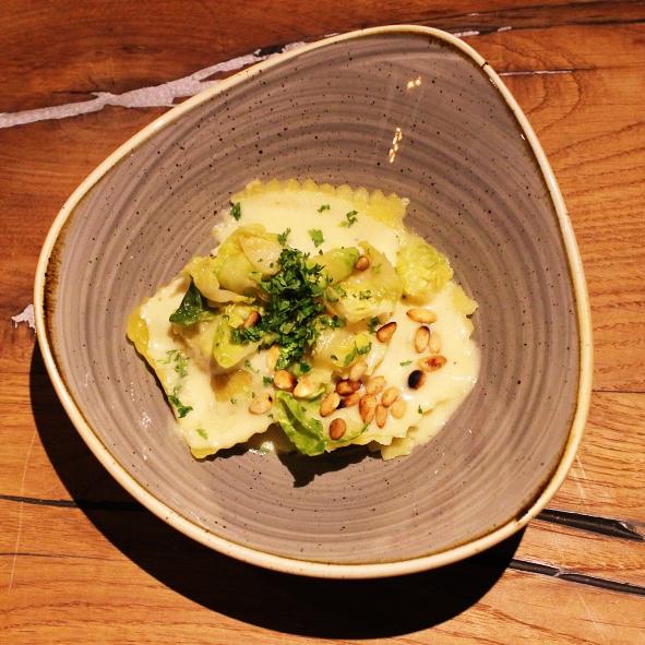Hausgemachte Ravioli mit Steinpilzfuellung Kerbelschaum mit Rosenkohlblaettern und Pinienkernen